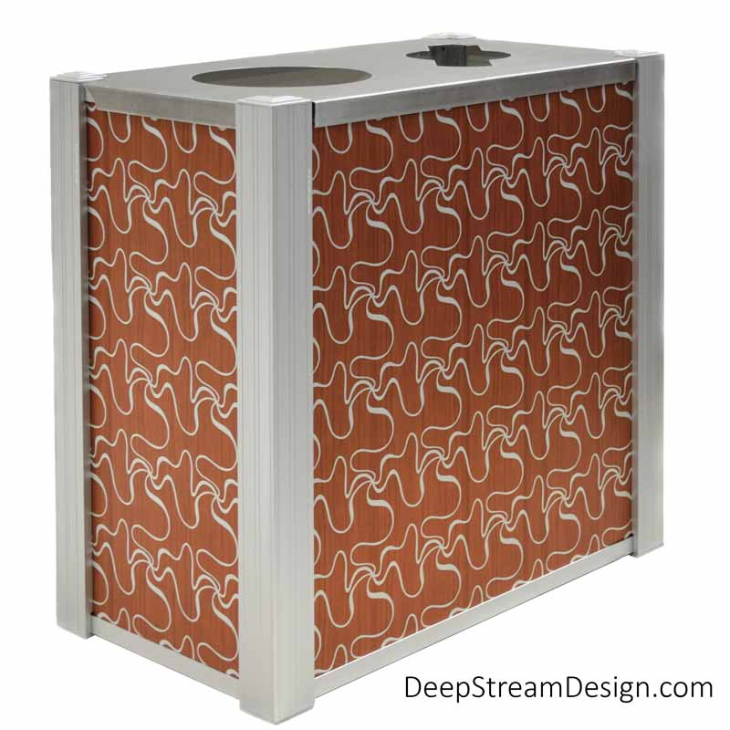 A studio photo of an Audubon dual-stream Modern Commercial Combined Recycling and Trash Receptacle with side panels using ATI Laminates Fusion Aluminum Panel with the Crossway pattern printed in silver on light cherry wood background as a panel option.