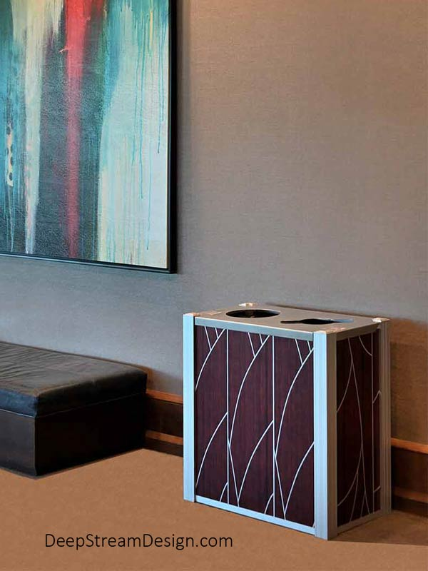 An Audubon dual-stream Modern Commercial Combined Recycling and Trash Receptacle, with side panels using ATI Laminates Fusion Aluminum Panel with the art deco Tree pattern printed in silver on dark cherry wood background, serves in an art-filled 5-star Hotel Lobby next to a black leather couch.