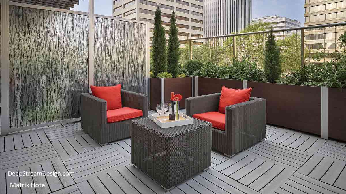 A large balcony or restaurant  privacy screen wall created with DeepStream's proprietary anodized Structural Architectural Aluminum Frame System and slide-in 3form Ecoresin panels with a Birch branch pattern, anchored by a Mariner commercial wood planter. There are 2 brown wicker chairs and a cube with red cushions and a red flower on a tray arranged a balcony of the Matrix hotel with high-rise buildings in the background.