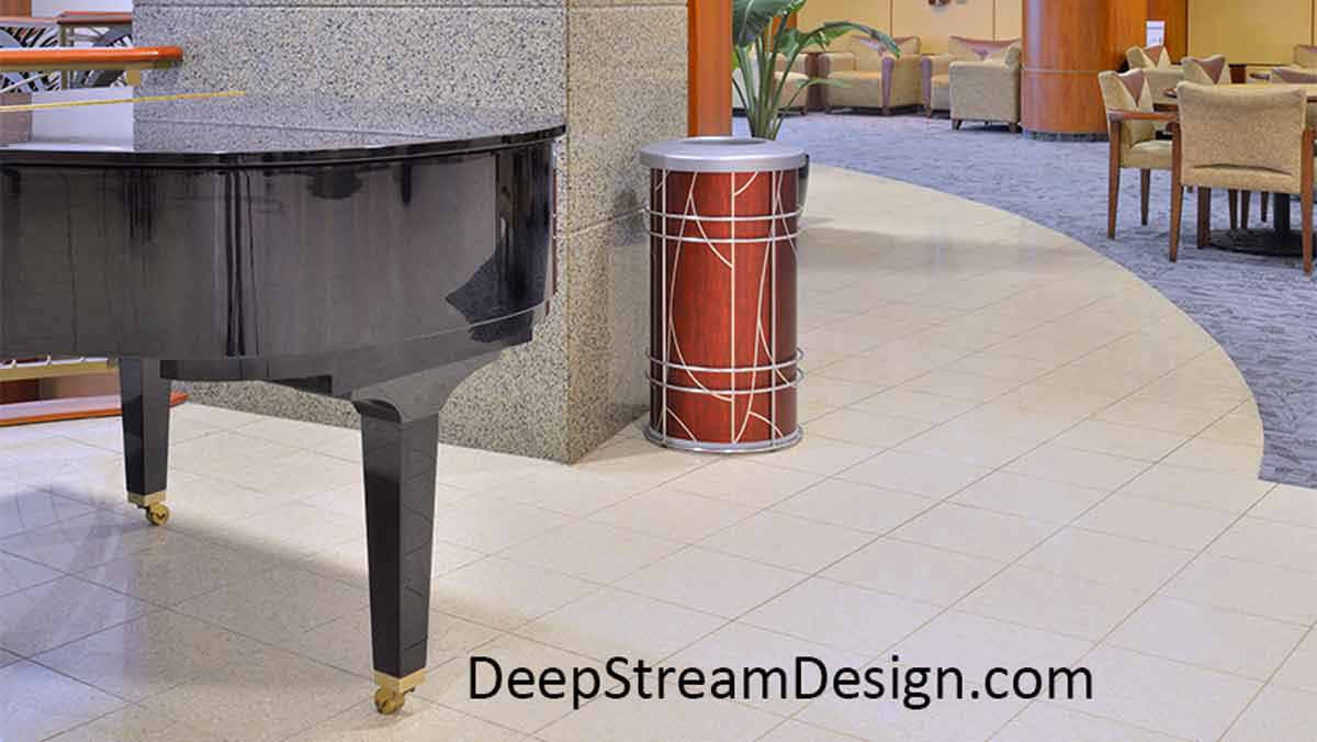 """Pictured in the lounge of an ultra-modern hospital complete with a black grand piano and inlayed tan tile and blue carpet floors and marble walls, the round Chameleon indoor modern receptacle is used by Designer's as a stylish trash bin or recycling receptacle wrapped with an ATI Laminates silver art deco """"Tree"""" graphic against a dark cherry wood background."""