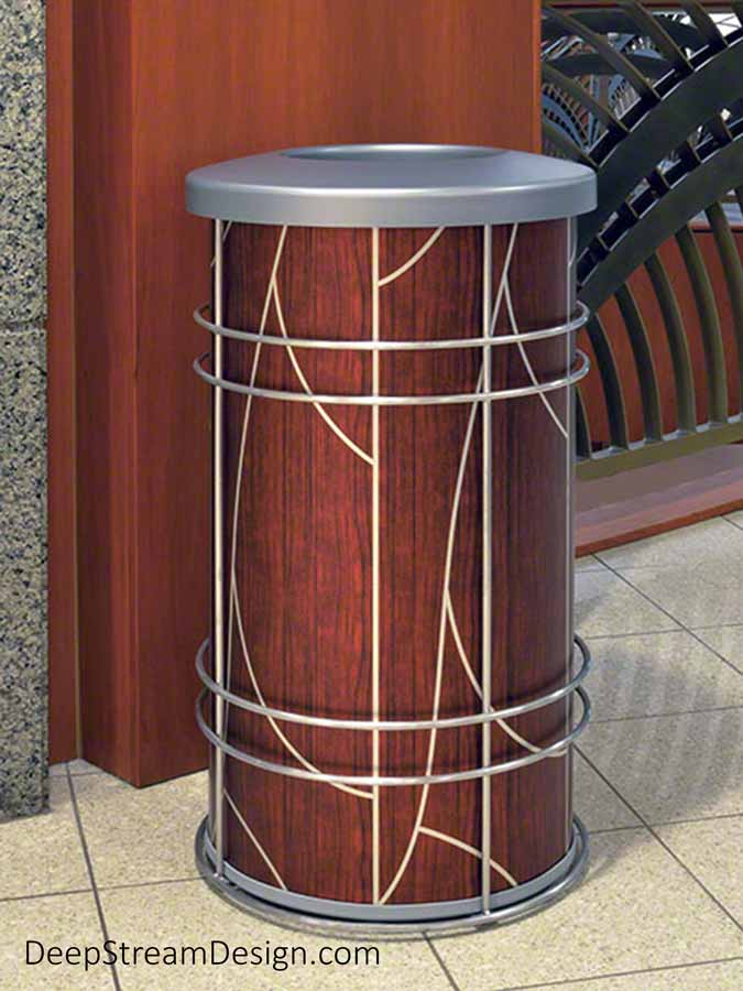 """Pictured in the lounge of an ultra-modern hospital, the round Chameleon indoor modern receptacle is used by Designers as a stylish trash bin or recycling receptacle wrapped with any graphic that fits your customer's project. Designed with a removable 15-gallon leakproof plastic inner liner surrounded by a fireproof metal liner to which we affix your graphic. Shown here with ATI Laminates modern silver art deco """"Tree"""" silver pattern against a dark cherry wood background."""