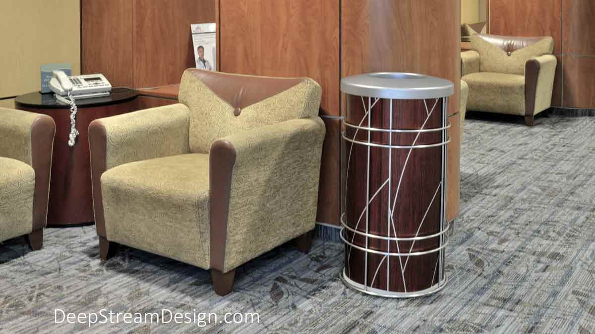 """Pictured in the lounge of an ultra-modern hospital, the round Chameleon indoor modern receptacle is used by Designers as a stylish trash bin or recycling receptacle wrapped with any graphic that fits your customer's project. Designed with a removable 15-gallon leakproof plastic inner liner surrounded by a fireproof metal liner to which we affix your graphic. Shown here with ATI Laminates art deco """"Tree"""" silver pattern against a dark cherry wood background."""