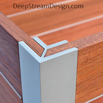 A photo showing DeepStream's Mariner anodized aluminum corner extrusion fitted with a tropical hardwood plank for a privacy screen wall.