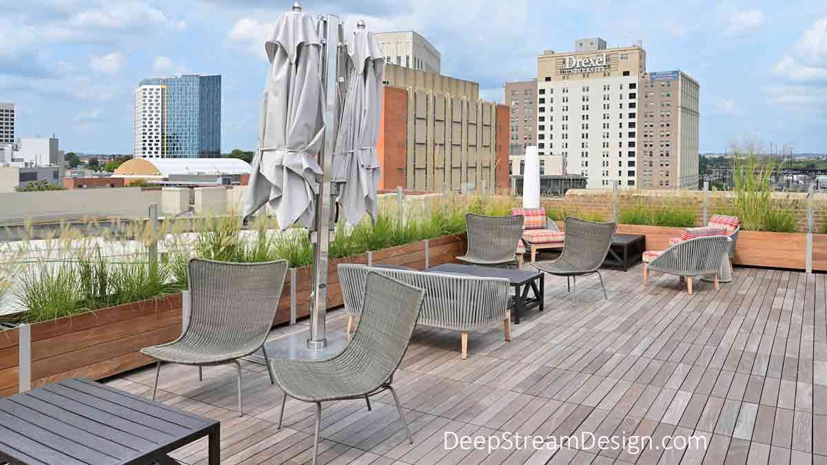 Glass Screen Wall anchored by landscaped long wood garden planters is used to create a parapet wall for safety that will also block the wind while not blocking the view, as seen here creating a seating area on an urban condo building lounging area.