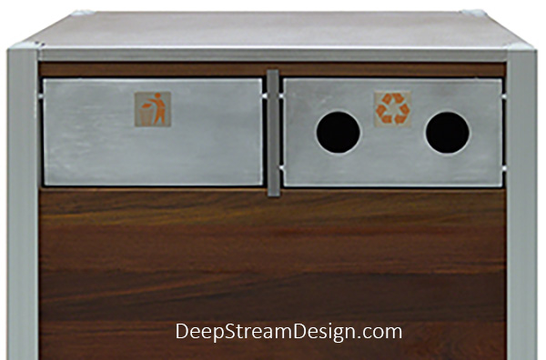 """Oahu dual-stream Modern Commercial Combined Recycling and Trash Receptacle with one swinging push flap for trash with the """"Keep Tidy"""" symbol badge for trash, and a fixed front flap option with two holes in the face that limit recycling acceptance to aluminum cans and plastic bottles with a Recycling Symbol Badge. Both Symbol Badges are 316 stainless steel and copper colored enamel."""