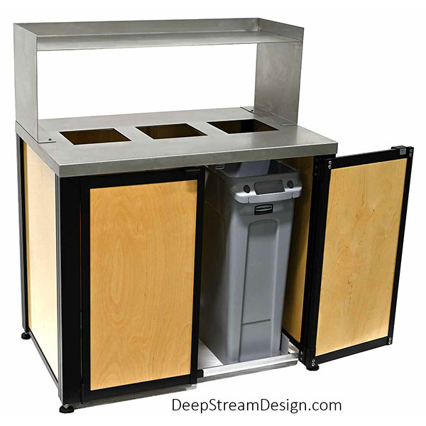 Studio photo showing an Oahu triple-stream Modern Commercial Combined Recycling and Trash Receptacle with light maple panels with optional double front doors to remove bins. Optional removable 14-gauge 316 stainless steel food tray return shelf mounted atop a 16-gauge 316 stainless steel lid with custom square cutouts for trash and recycling as indicated by optional Nameplates and Symbol Badges.
