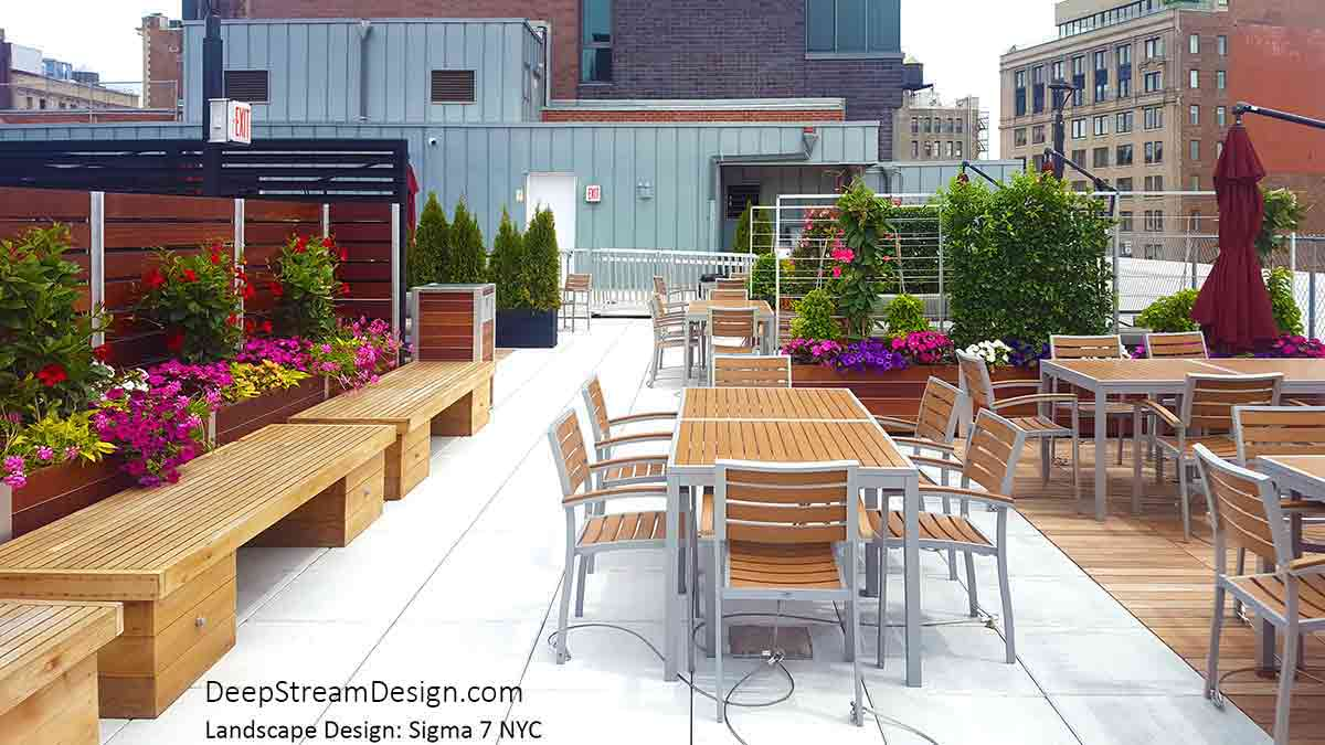 An urban rooftop restaurant uses wood Outdoor Restaurant Privacy Screen Wall, anchored by DeepStream Mariner Restaurant Planters colorfully landscaped overflowing with bright red and white flowers and crawling vines, to create the waiting and dining sections. Trellis Screens between tables, with green vines and pink flowers, are also anchored by Mariner Restaurant Planters, providing a private natural dining experience for customers. The restaurant dining area is also served by DeepStream's Oahu Modern Commercial Trash Bin and Recycling Receptacle.