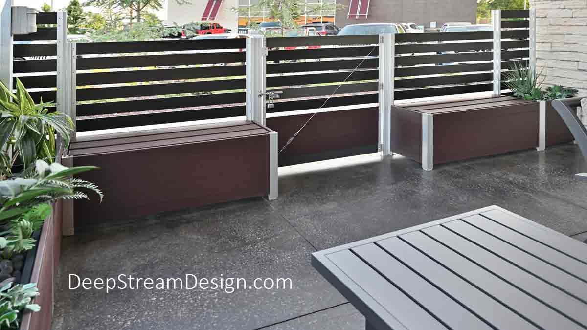 A detailed interior view of an outdoor restaurant screen wall with a gate used to create the restaurants outdoor smoking section. Anchored by Ipe Brown Mariner commercial wood restaurant planters crafted of maintenance free recycled plastic lumber which hold slid-in easy anodized aluminum screen wall panels.