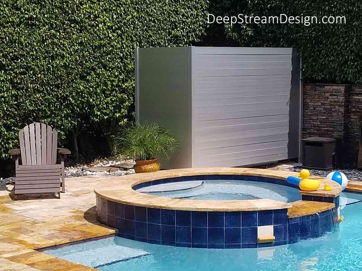 The homeowner of this beautiful backyard turquoise pool, spa and sundeck with a flagstone wall and tall dark green Ficus hedge used DeepStream's cost-effective 2-sided 8' tall Pool Equipment Screen in an L shape to hide the pool pump, heater, filter, and electrical utilities. The placement of the Pool Equipment Screen allows a hidden entry behind the screen and the lightweight silver aluminum planks are arranged in 3 slide-out-easy panels for full 360° instant access to all equipment.