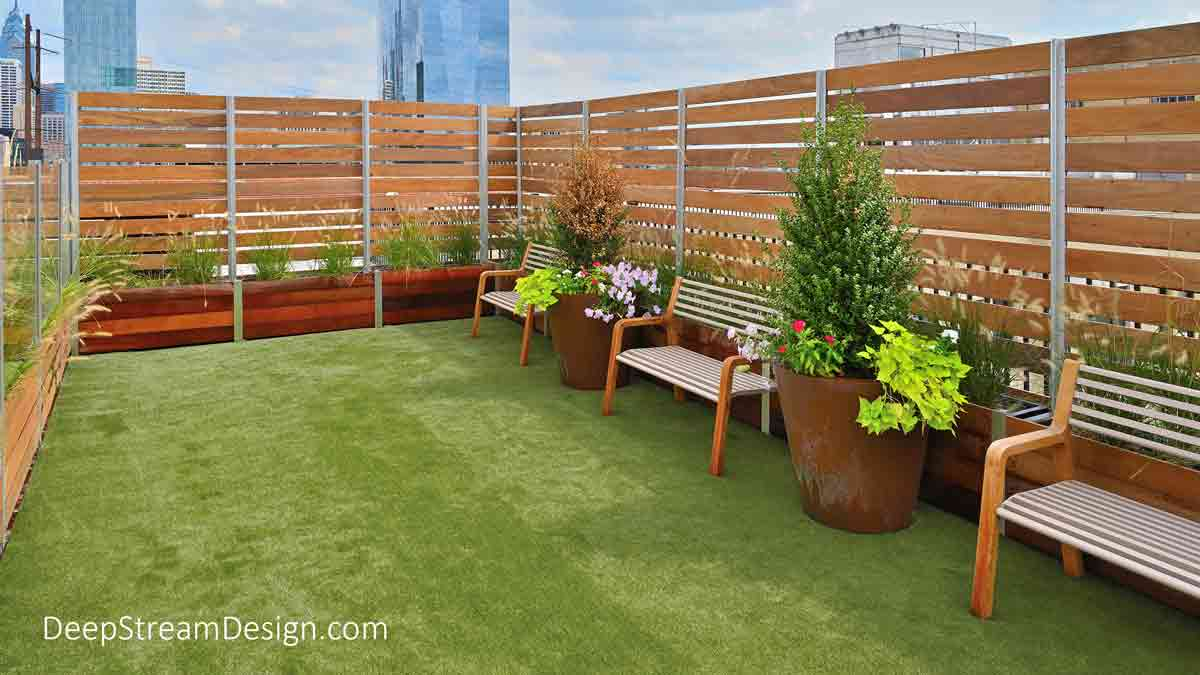 The interior view of a Rooftop Dog Park enclosure with landscaped planters, benches, and bright green turf created with DeepStream's Long Wood Garden Planters and Glass and Wood Privacy Screen Wall atop a naturally landscaped apartment building roof deck with the central high-rise financial district of a dense urban city in the background.