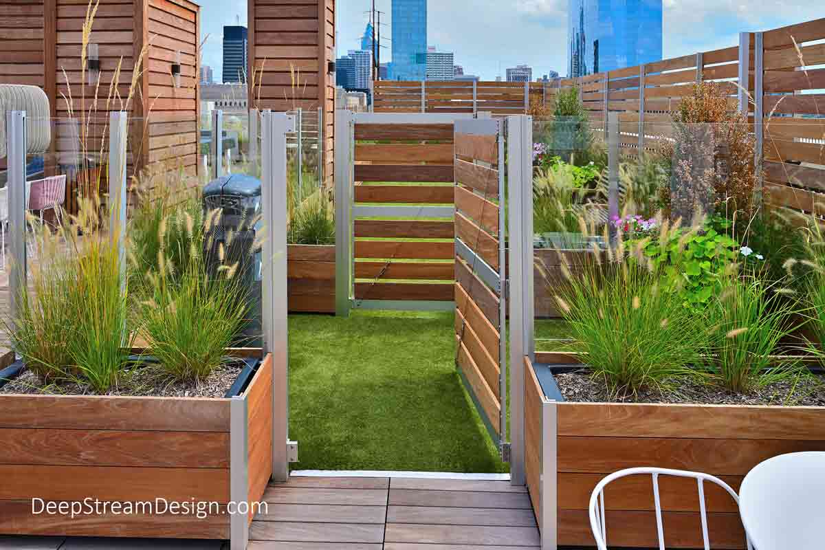 """A detailed interior view of a Rooftop Dog Park's double gated animal control area, or """"bull pen,"""" created with outdoor privacy screen wall that allows dogs to be let off leash or put on leash while in a confined area, as found at professionally designed dog parks."""