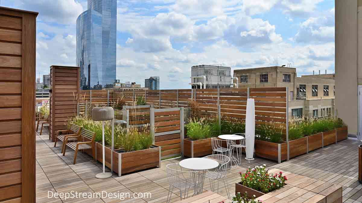 The exterior view of a nicely crafted and landscaped apartment building roof deck created with DeepStream's Long Wood Garden Planters and Privacy Screen Wall Enclosure creating a Rooftop Dog Park with the central high-rise financial district of a dense urban city in the background.