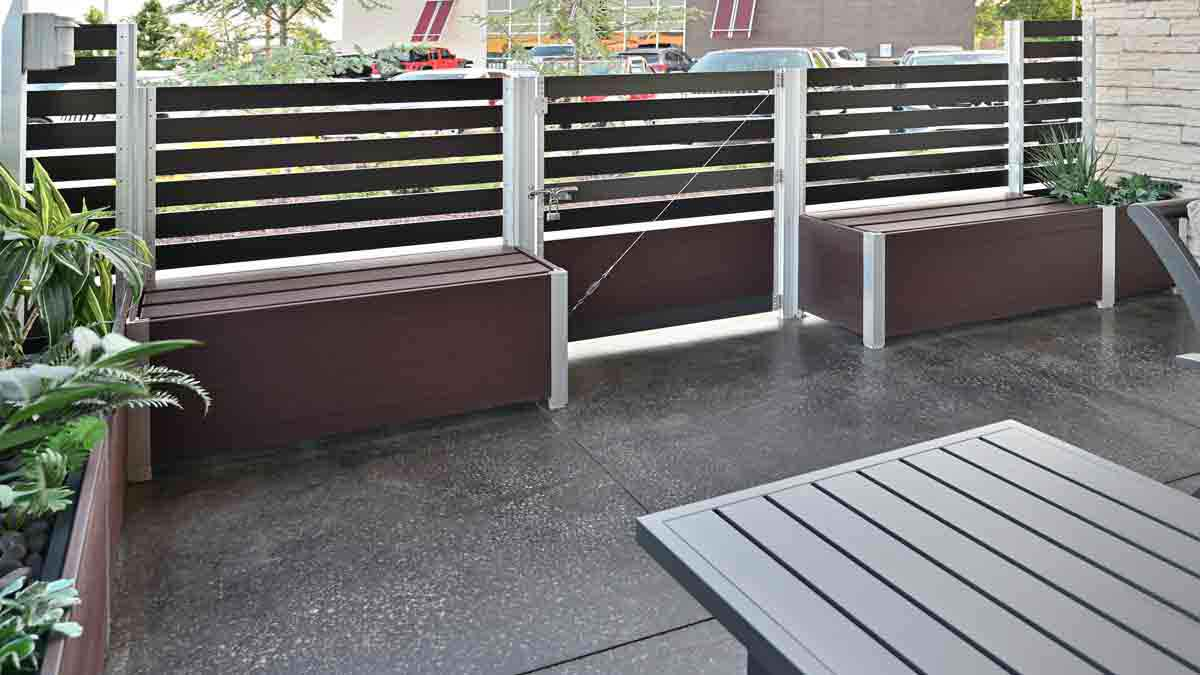 Two Ipe Brown recycled plastic lumber storage box benches with lift-off lids supporting a gate and privacy screen wall of an outdoor restaurant's seating area enclosure.