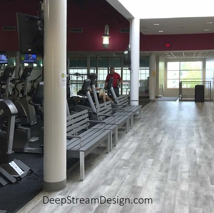 A picture of The Perfect Modern Bench with Back and Armrests crafted from Dark Gray recycled plastic lumber with 2 more benches inside a gym in front of a line of exercise machines.