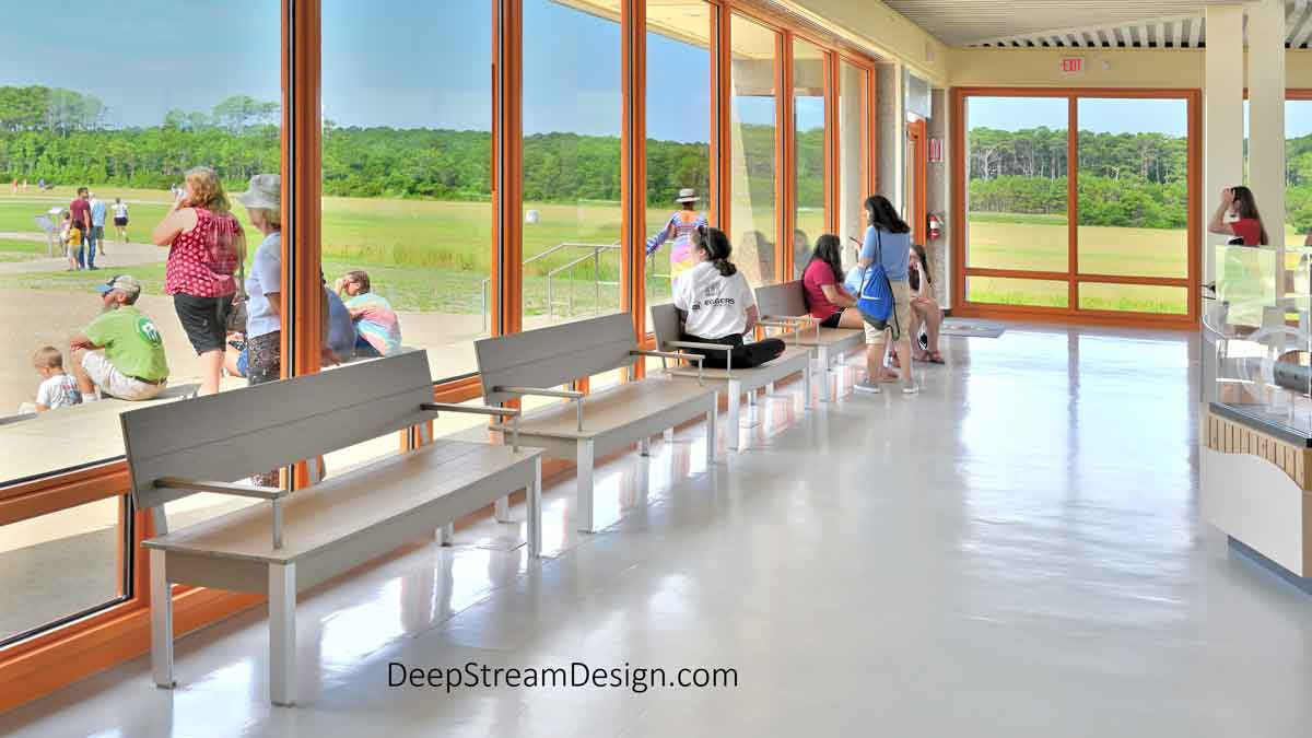 The Perfect Modern Bench with Back, armrest, and solid seat 72 inches long in a row of four, crafted with Aged Hardwood recycled plastic lumber, serves visitors inside the Wright Brothers National Memorial Museum building as they look out the windows at the historic sand track runway where the brothers took their first historic flight in their plane, the Kitty Hawk.