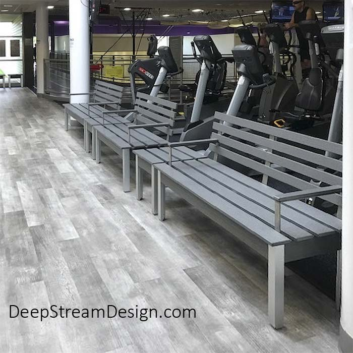 A picture of The Perfect Modern Bench with Back and arm rests crafted from Dark Gray recycled plastic lumber with 2 more benches inside a gym in front of a line of exercise machines.