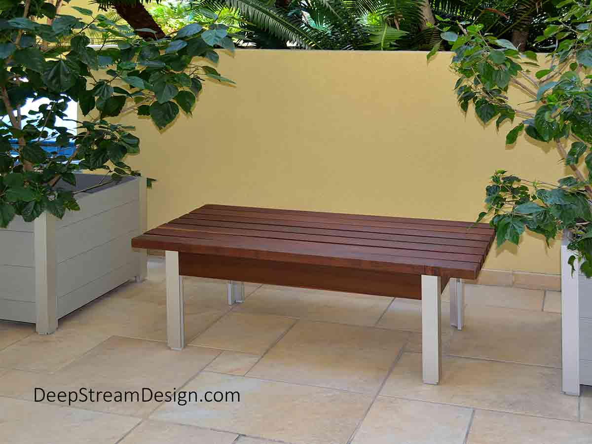 The Perfect Outdoor Bench, ergonomic sustainable design, crafted of dark brown Ipe tropical hardwood and silver marine anodized aluminum, photographed sitting outside on natural golden stone pavers in the courtyard entrance of a modern building flanked by large potted tropical bushes in front of a large built-in garden planter overflowing with lush dark green tropical ferns and coconut palms.
