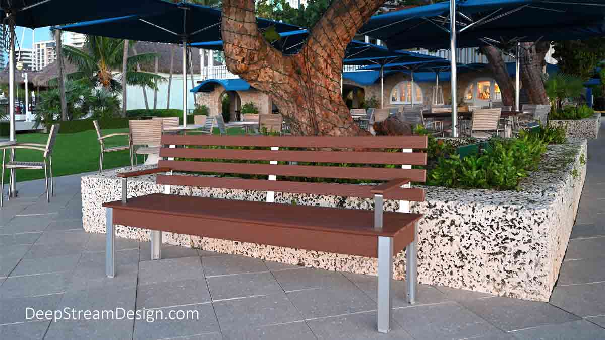The Perfect Outdoor Bench in a 72-inch version crafted from Tropical Hardwood-colored recycled plastic lumber with silver anodized aluminum legs and 316 stainless steel arm and back supports pictured in use at a tropical oceanfront Miami yacht club dining terrace.