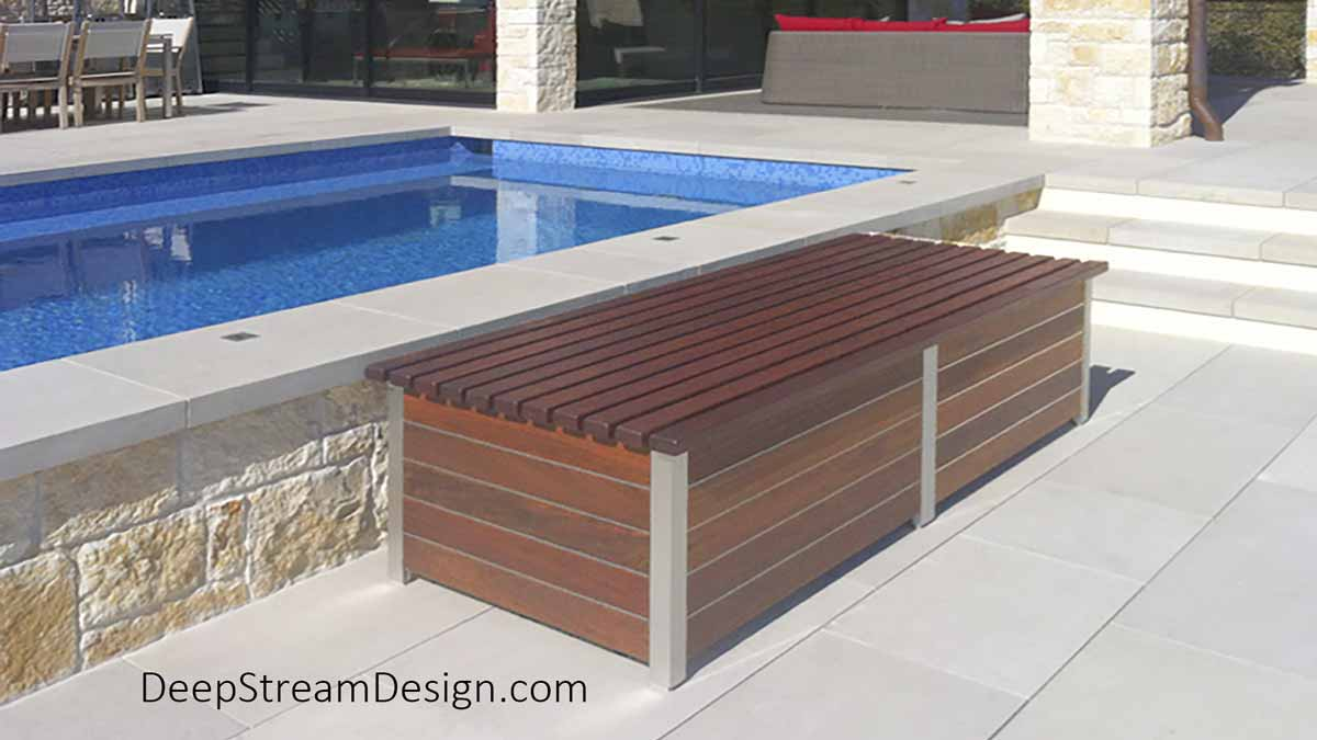 """The Perfect Deck Box bench is a 6' long outdoor Ipe deck box with hinged lid at bench height. The deck Box is crafted with of reddish-golden Ipe wood planks separated by 1/8"""" silver zephyr aluminum bands creating a distinctly modern deck box as seen here next to a bright blue 2-level pool of an ultra-modern home built of natural stone on several levels cut into the hillside overlooking Austin Texas."""