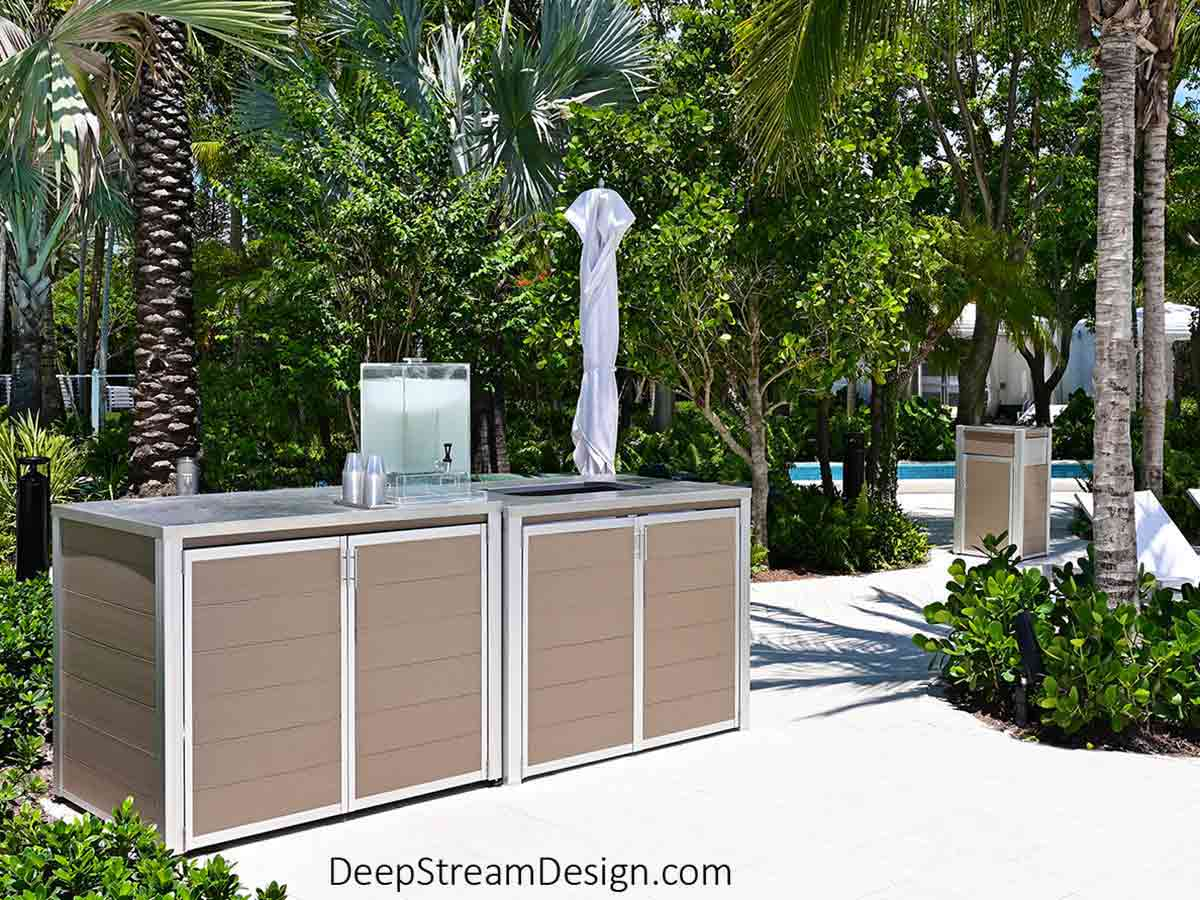 """In an idyllic tropical setting, a calm stretch of the turquoise blue """"Lazy River"""" winds itself between towering coconut palms and verdant green vegetation where swimmers enter the water next to a Large Modern Outdoor Trash Can and matching Weatherproof Pool Towel Cabinets and Return Cart Enclosure crafted with no-maintenance aged hardwood-colored recycled plastic lumber, 316 stainless steel, and marine anodized aluminum."""