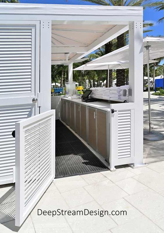An all-white outdoor activities center under a canvas top at a tropical resort's waterpark has modern Weatherproof Pool Towel Issue Cabinets with locking front drawers above them just under the weatherproof counter.