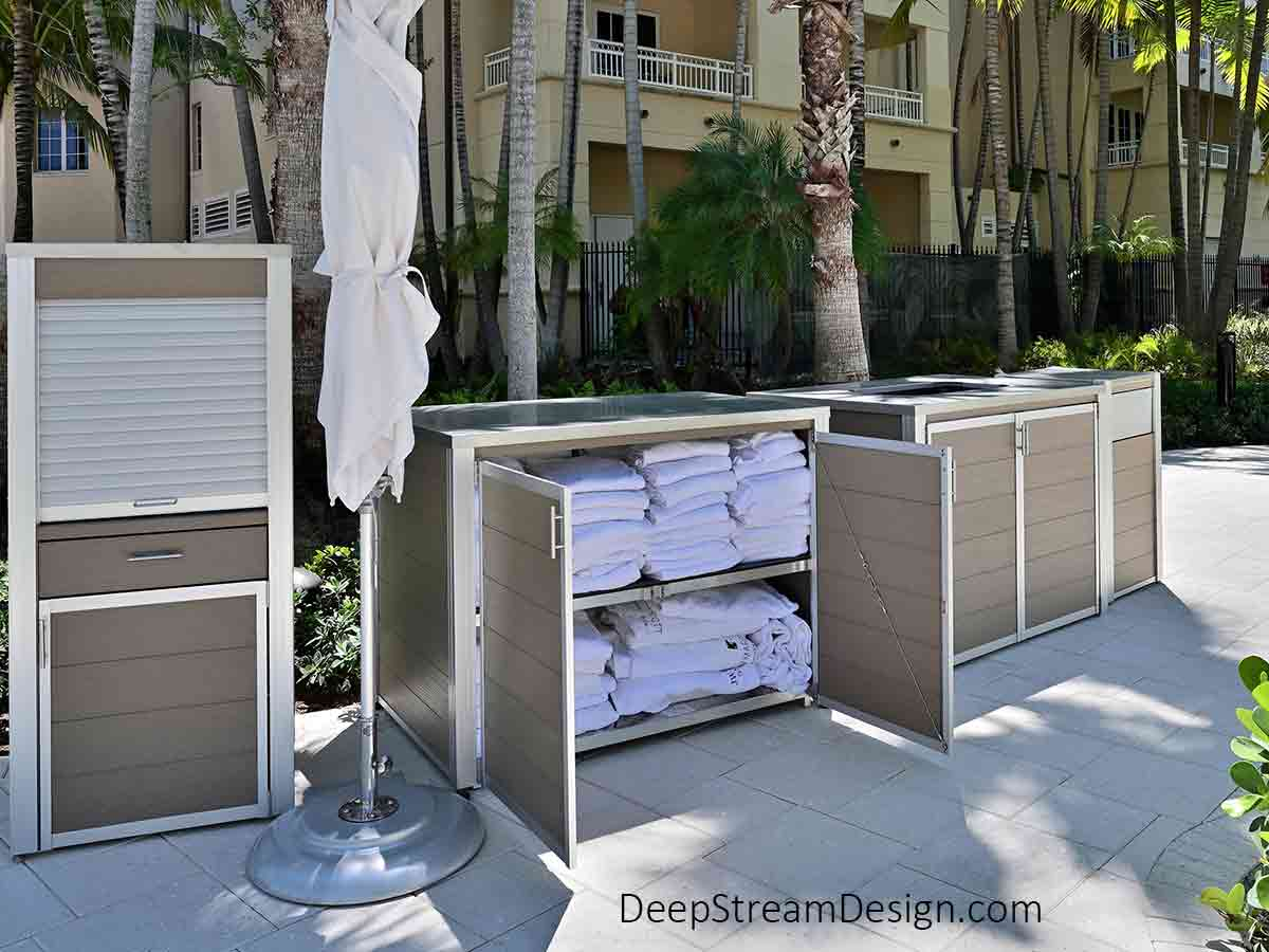 Pictured on the natural white stone pool deck of a tropical water park with palm trees, green bushes, and a wing of the resort hotel behind it, a Weatherproof Pool Towel Issue Cabinet is shown with its wide double doors open revealing waterproof shelves filled with neatly folded white pool towels for guest self-service. A Weatherproof Towel Return Cart Enclosure and a Weatherproof Enclosure for Point-of-Sale Systems flank it on either side while a Large Oahu Commercial Modern Trash Can stands slightly apart. All four waterproof cabinets and fixtures feature Aged Hardwood-colored recycled plastic lumber side panels and doors, 316 stainless steel lids and proprietary marine anodized aluminum frames so they may be pressure cleaned for sanitation, as there is no paint or powder coating to fail.