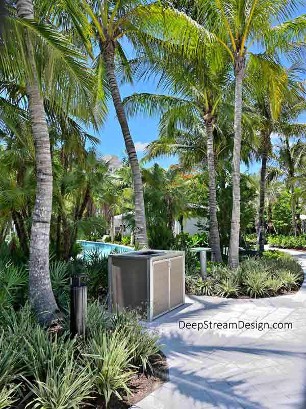 """An idyllic tropical setting at a calm stretch of the turquoise blue """"Lazy River"""" winding itself between towering coconut palms and verdant green vegetation where swimmers entering the water next to a Weatherproof Towel Return Cart Enclosure crafted with no-maintenance aged hardwood colored recycled plastic lumber, 316 stainless steel, and marine anodized aluminum."""