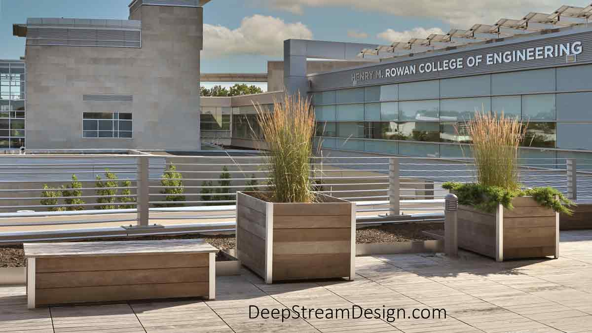 A commercial wooden storage box bench on the rooftop deck of the at Rowan College of Engineering next to two DeepStream Mariner commercial wood planters.