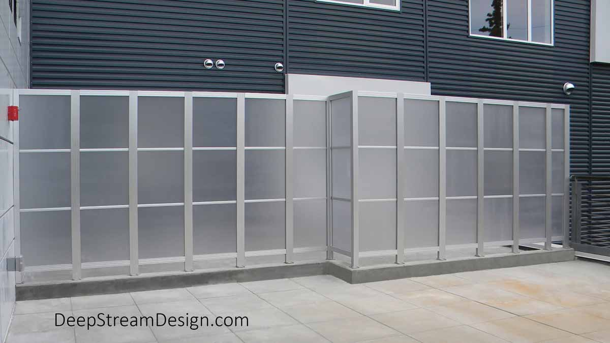A long screen wall comprised of smaller widow of frosted Lexan polycarbonate created with DeepStream's proprietary anodized Structural Architectural Aluminum Frame System. This High-Wind Screen Wall was created for an Alaskan housing project with gray siding to create a balcony privacy screen that would withstand 145 MPH gusts of wind coming off a glacier.