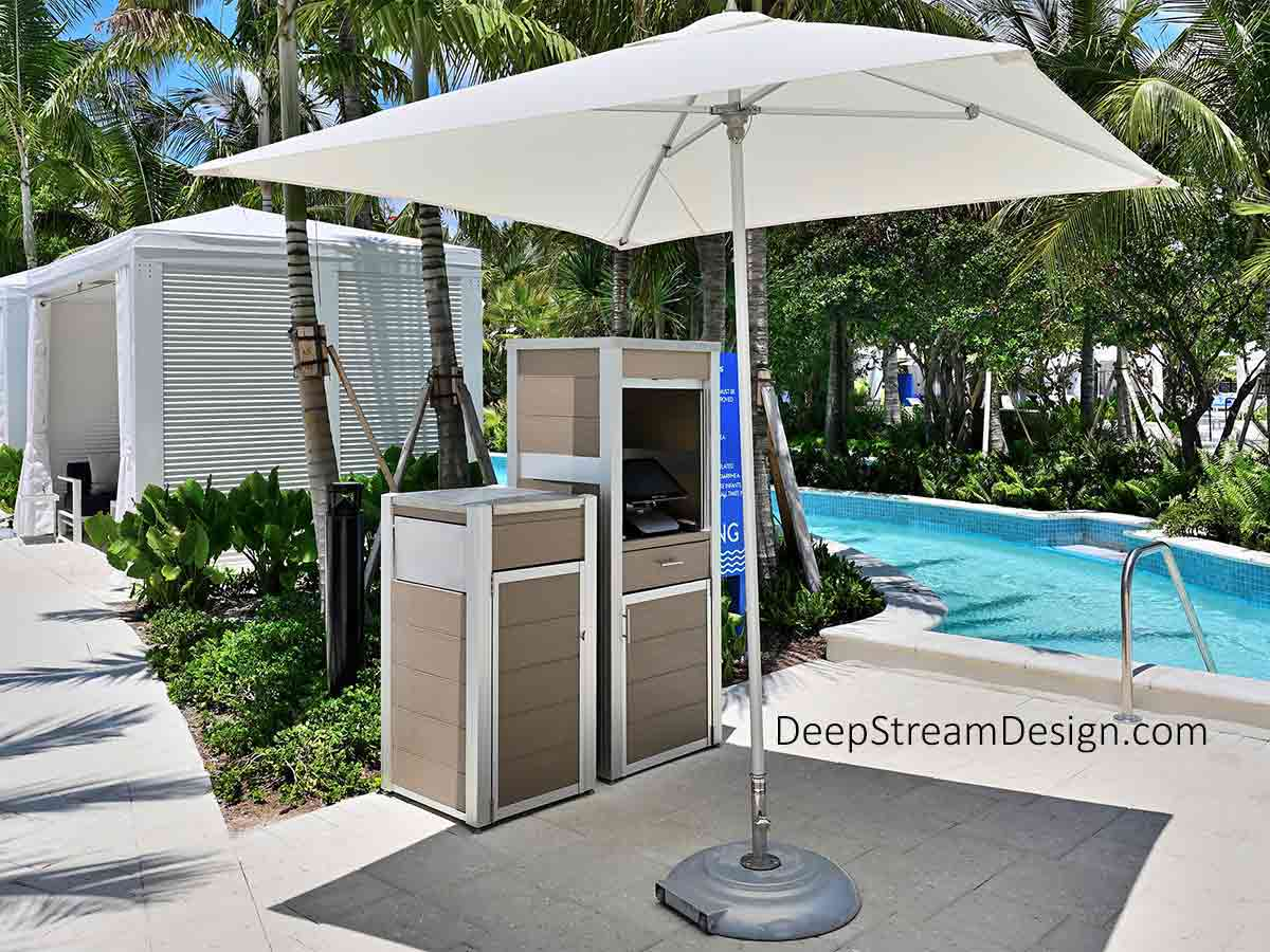 """A Weatherproof Enclosure for Point-of-Sale Systems at a 5-Star hotel's award-winning tropical water park, located far from the kitchen and bar at a turn in the waterpark's azure blue """"lazy river,"""" under palm trees near private cabanas, stands next to a ready to speed orders, improving the guest experience, while increasing revenue and lowering labor costs. The waterproof cabinet housing the POS system has an anodized aluminum tambour door and 316 stainless steel lid, and is located next to a large commercial modern trash can that also has a stainless steel lid and anodized aluminum frame. Both resort pool fixtures are crafted with environmentally friendly aged hardwood-colored recycled plastic lumber and designed to withstand tropical downpours."""