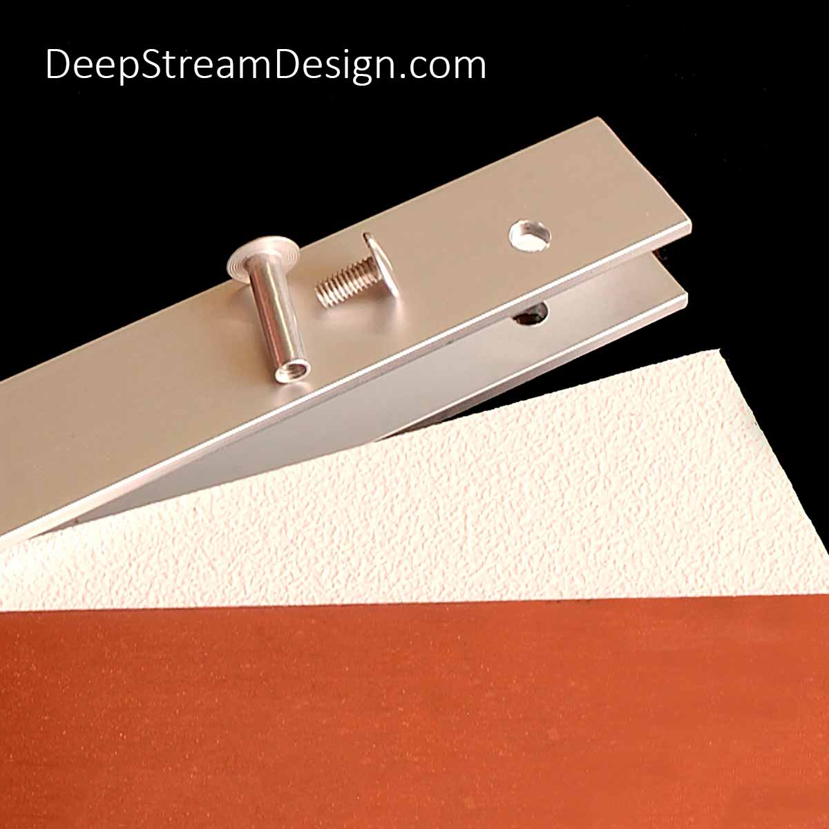 A Studio photo of a proprietary Audubon Aluminum Frame System U-channel creating a composite panel using a thin sheet of expensive copper with an inexpensive white panel in the background.