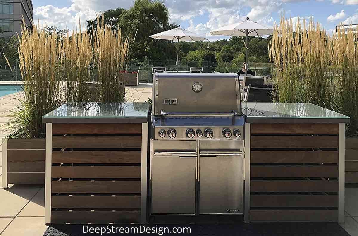 Custom-crafted BBQ Grill Surround on a rooftop pool terrace landscaped with DeepStream commercial wood planters growing tall ornamental grass. The BBQ Grill Surround aluminum frames, resting on HDPE non-scuff, are built to support any countertop material, shown here with glass over concrete, and to any dimension, lined with fire-proof aluminum sheeting with wood plank enclosures with solid or spaced plank panels.