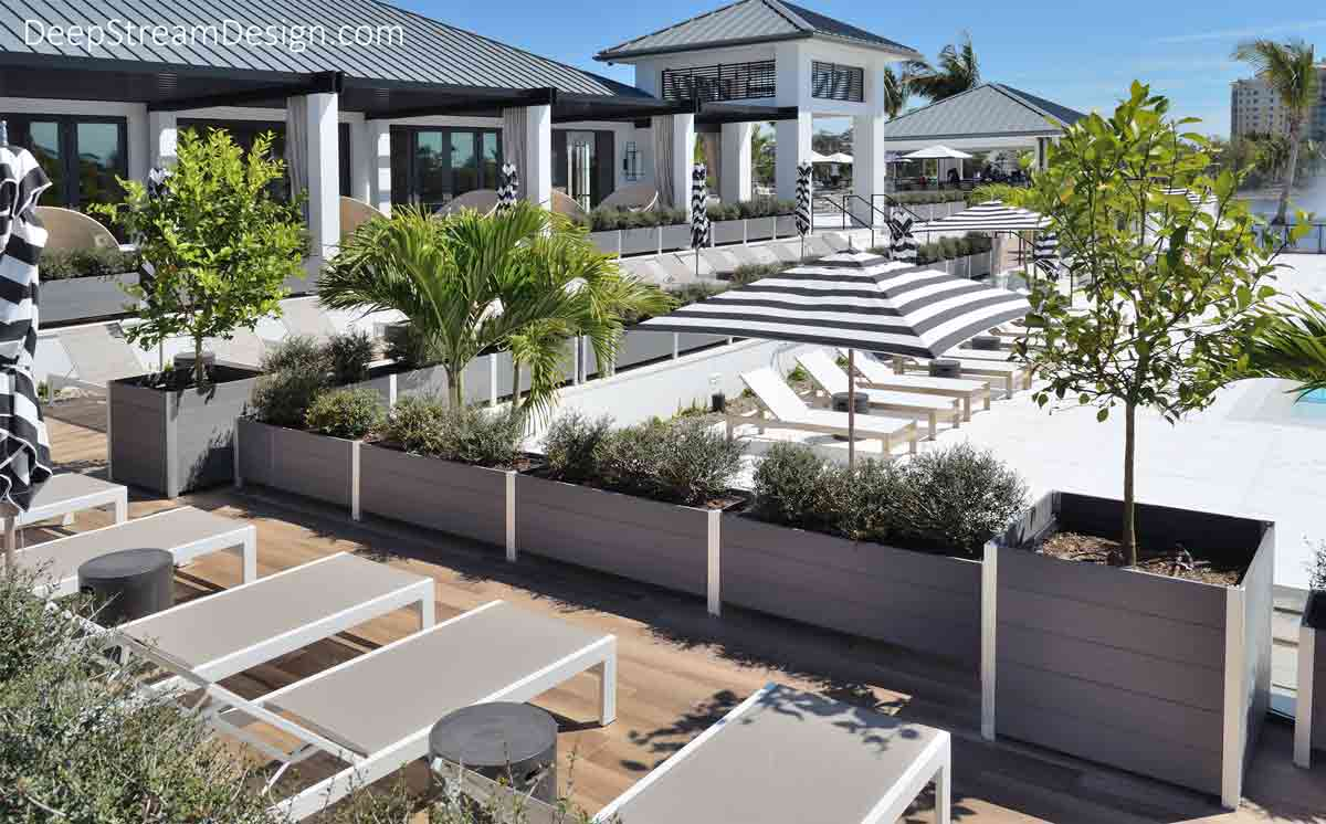 A resort with multiple levels of terraces for clubhouse dining and sunbathing on white lounge chairs under grey and white striped umbrellas, above a turquoise blue swimming pool. Long, rectangular, modern light grey recycled plastic commercial wood planters and large square planters for trees create green landscaped living parapet walls for safety between terraces.