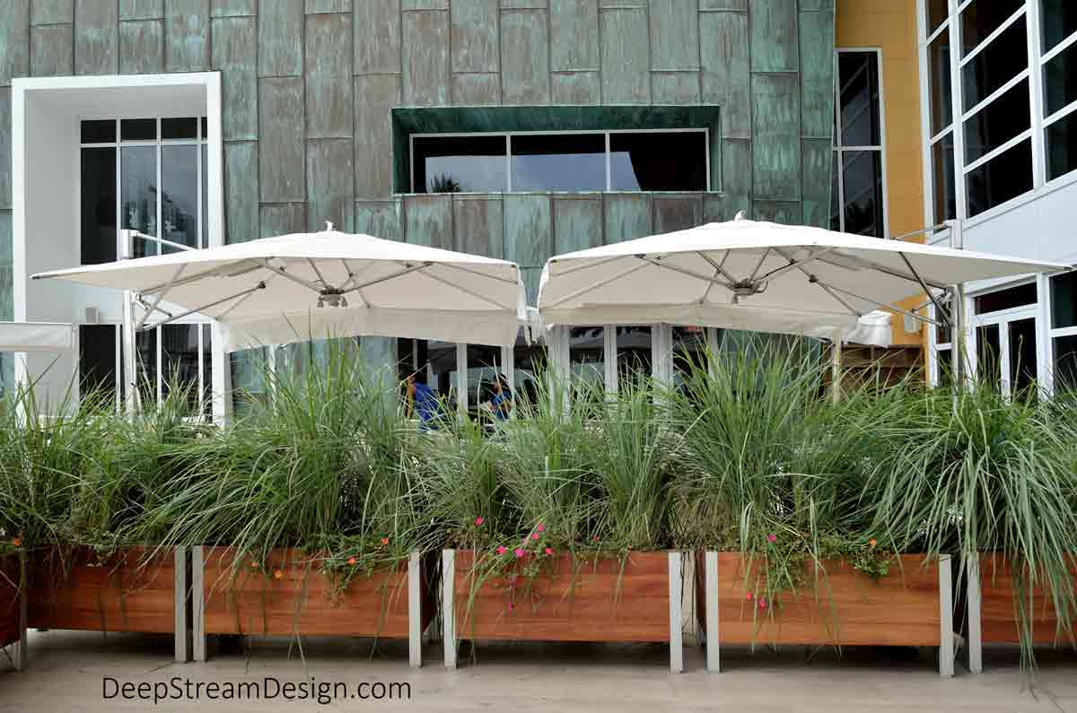 Large wood commercial planters, landscaped with tall flowering ornamental grasses, create a living privacy screen between a Mandarin Oriental resort's dining terrace with tables under large white umbrellas and a public waterfront walkway.