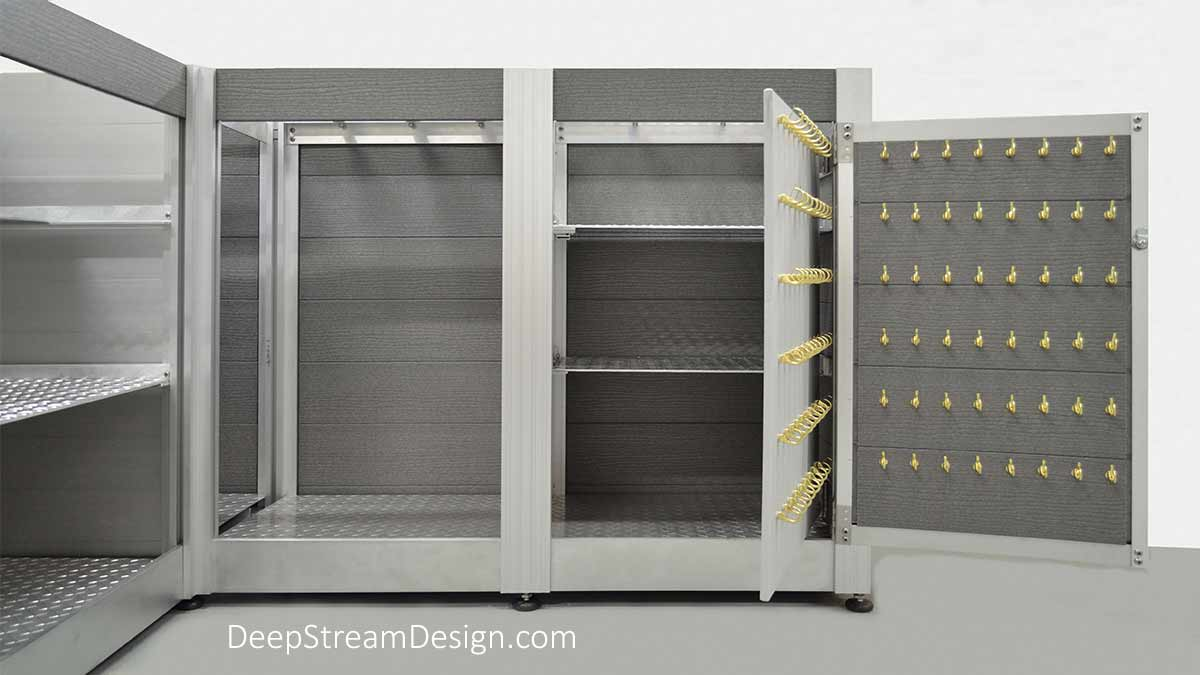 This studio picture shows the detail of a space for one or two mini fridges and the large valet key locker, with a locking door and a hidden compartment behind the key locker, that are part of a large L-shaped Valet Parking Stand / Outdoor Reception Desk. The weatherproof fixture is constructed with DeepStream's proprietary marine anodized aluminum frame, maintenance-free light grey recycled plastic lumber planks, and stainless steel. The countertop has been removed to show the aluminum flat bar and angle supports for the 316 stainless steel countertop, mini-fridge and key locker compartment.