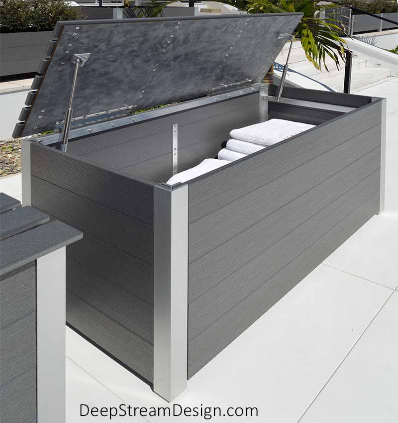 A look inside a Modern Large Custom Wood Outdoor Deck Box, full of large white folded pool towels, crafted from dark gray colored weatherproof HDPE recycled plastic lumber. The waterproof lid is shown opened on proprietary 316 stainless steel hinges and held in open by a stainless steel gas spring at each end which allows the lid to be lifted effortlessly, even by children. These gas springs hold the lid open without fear of it closing on your fingers.