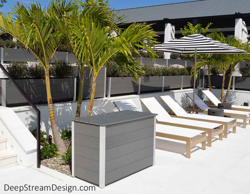 A Modern Large Custom Wood Outdoor Deck Box, crafted from dark gray colored weatherproof HDPE recycled plastic lumber to hold pool towels, sits next to a long row of white sunbeds shaded by large blue and white striped umbrellas. The modern waterproof deck box complements the Mariner large wood planters on the multi-level terraces facing a large swimming pool and spray fountain for kids.