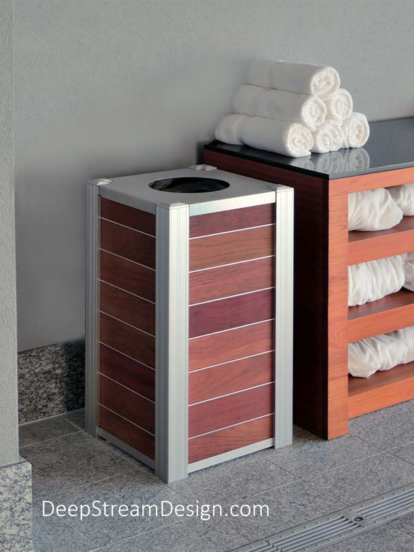 Pictured at 5-star resort spa, the striking modern presence of this compact, Jatoba tropical hardwood, anodized aluminum and 316 stainless steel spa towel return bin creates an immediate impression of substance and luxury. Optional Zephyr aluminum banding separates the golden red hardwood planks to heighten the modern design of this deluxe towel return fixture.