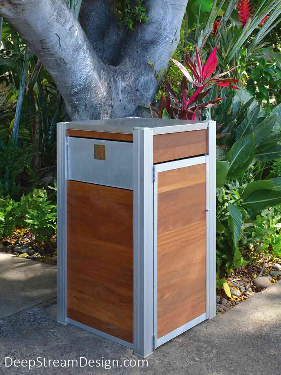 An Oahu Modern Commercial Recycling and Trash Bin is pictured at a tropical island's verdant garden restaurant on a beach. Handcrafted in America using Cumaru tropical hardwood, hinged 316 stainless steel lid and hinges for the ergonomic side door used for bag changes, an aluminum push flap to match the silver anodized aluminum legs keep out the rain and birds.