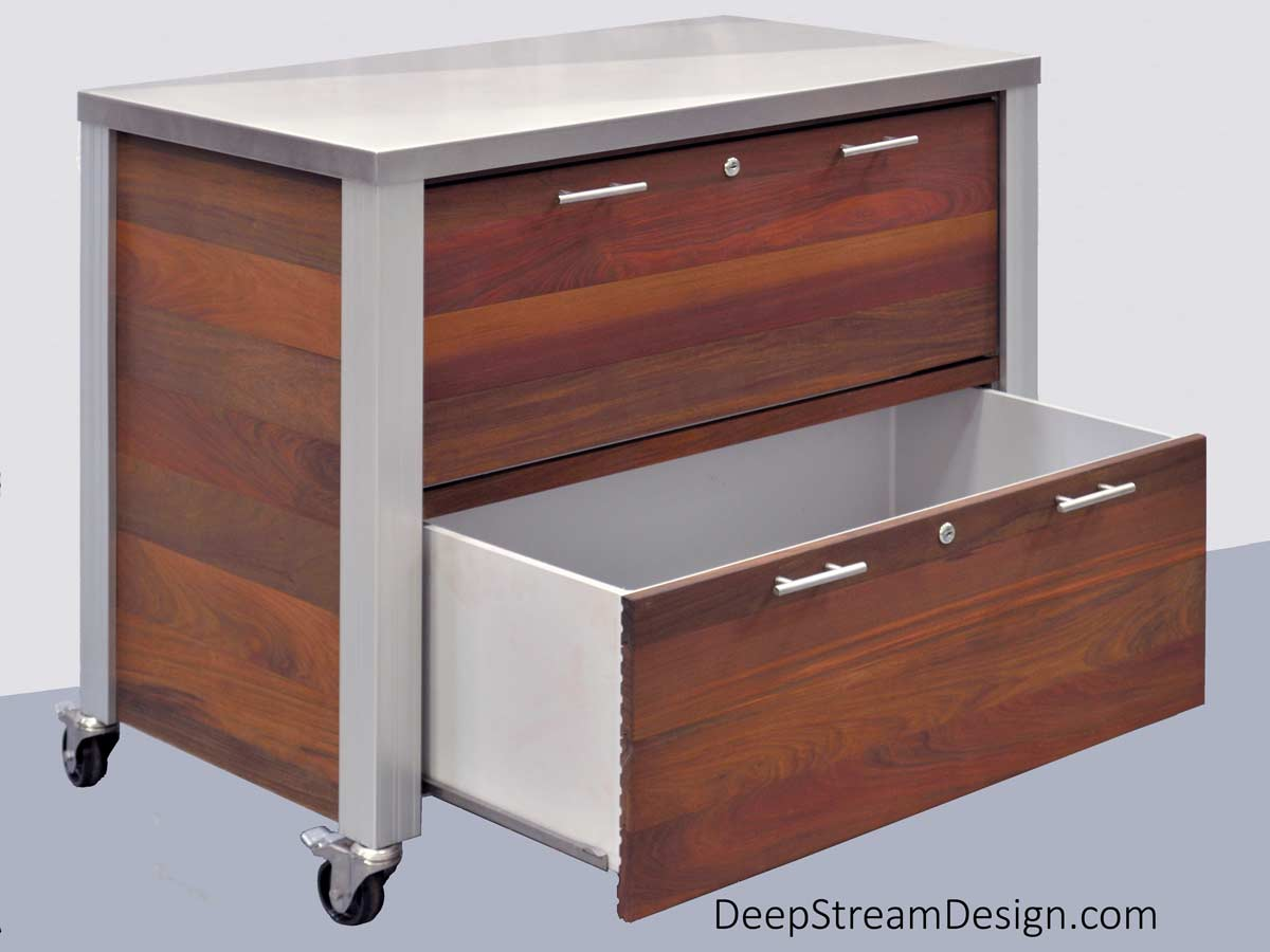 Studio photos of a weatherproof Ipe tropical hardwood Outdoor Restaurant Food Service Cabinet with two waterproof hygienic HDPE drawers and 316 stainless steel countertop, on stainless steel casters with polyolefin wheels. The bottom drawer is partially open to reveal the inside of the drawer.