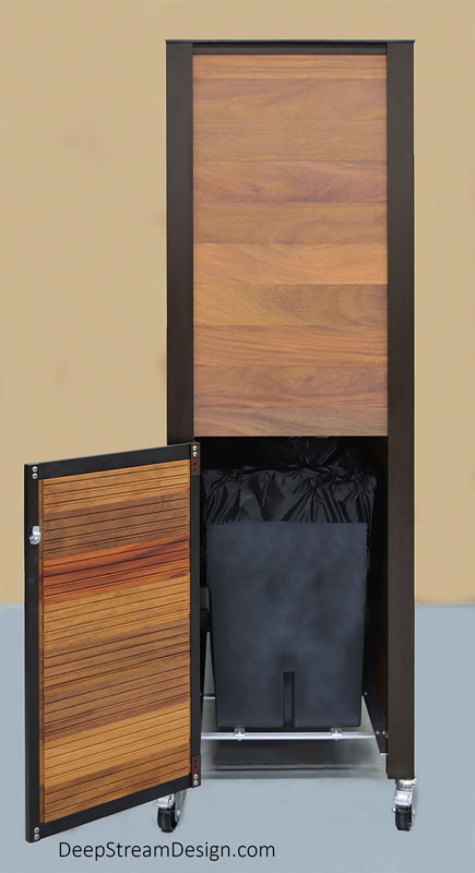"""Studio picture taken from the side of a large, finely constructed, rolling golden brown tropical hardwood custom Outdoor Restaurant Waiter and Bussing Station on stainless-steel caster wheels with a counter height enclosure hiding a leakproof trash and used linen bins accessed by round holes with signs in the countertop. In this picture you see the cabinet side walls planks, door hinges and latch are held by 72"""" tall Bronze anodized DeepStream proprietary aluminum extrusion. The door to remove the black trash and used linen bins is open on this end showing the bins resting on an open aluminum grid that gives no place for dirt or towels to hide."""