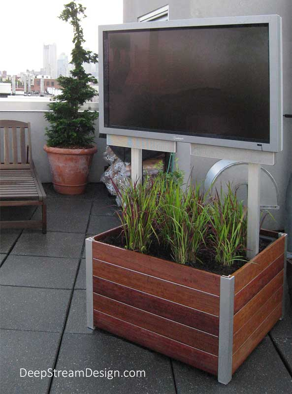 A truly robust Mobile Outdoor TV Stand makes this 42-inch outdoor weatherproof TV stable in windy conditions, even on a rooftop terrace. The key to creating a stable, but portable, large TV is to mount it to a Garden Planter on wheels. The low center of gravity and weight of the planter, mounted on stainless steel caster wheels with brakes, more than compensates for the weight and windage of the TV. DeepStream's modern Mariner commercial wood planter is crafted from Cumaru wood with Zephyr aluminum banding between planks. The proprietary anodized structural aluminum legs of the planter are attached to the interior aluminum frame which is engineered to hold both the rugged wheels and the uprights that hold the TV's VESA mounting plate and serve as the wiring chase to hide the wires of this elegant fixture. Completing the assembly is DeepStream's waterproof planter liner with advanced drainage options, landscaped with low flowers.