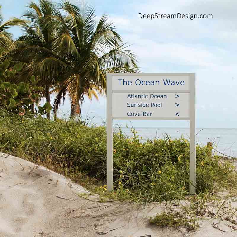 A Quick-Change Freestanding Sign for gives directions to a resort's shoreside amenities. The weatherproof sign is embedded in a small sand dune with yellow native flowers growing around the base, with tall sea grass, swaying palm trees, and ocean visible just behind it.