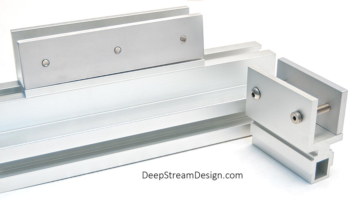 Studio photo of 3-inch and 6-inch heavy-duty anodized slide-in-easy panel clips engineered to distribute clamping forces allowing any material, in any thickness, to be used for panels with the Audubon Structural Architectural Aluminum Frame System.