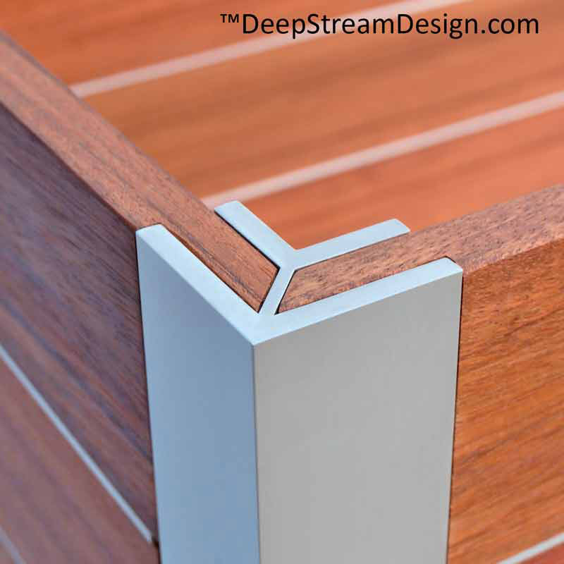 A studio photo looking showing an example of a Mariner Structural Architectural Aluminum Frame System L corner extrusion joining two mitered tropical wood panels at 90 degrees to form a large commercial wood planter box.