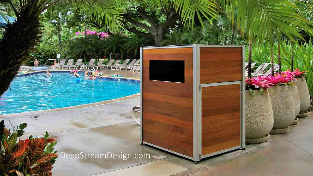 DeepStream custom crafts Weatherproof Pool Towel Cabinets and Return Cart Enclosures, using the Audubon Structural Architectural Anodized Aluminum Frame System, like this one in Ipe wood at a jungle pool of a tropical island resort.