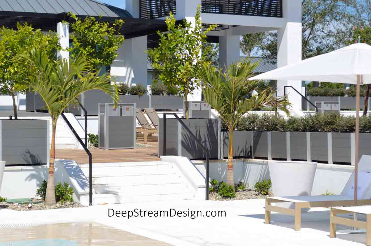 A resort with multiple levels of terraces for clubhouse dining and sunbathing on white lounge chairs under large white umbrellas, above a turquoise blue swimming pool. Long, rectangular, modern light grey recycled plastic commercial wood planters and large square planters for trees create green landscaped living parapet walls for safety between terraces. Modern Commercial Combined Recycling and Trash Receptacles crafted from recycled plastic lumber add to the guest experience.