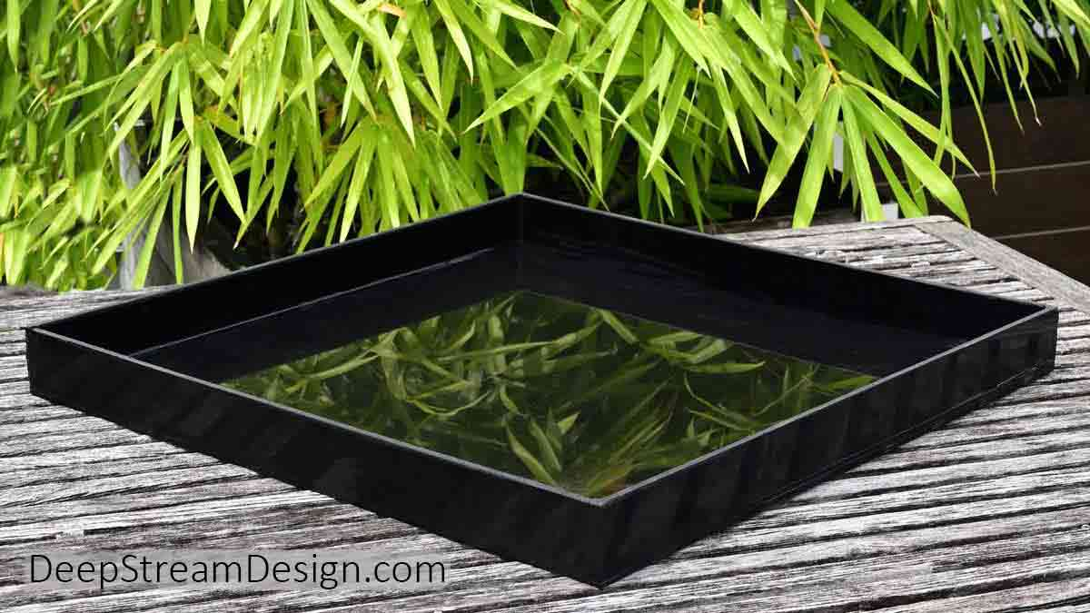 A black square Custom Welded Plastic Drip Tray shown on a table set in front of bamboo on a tropical roof deck.